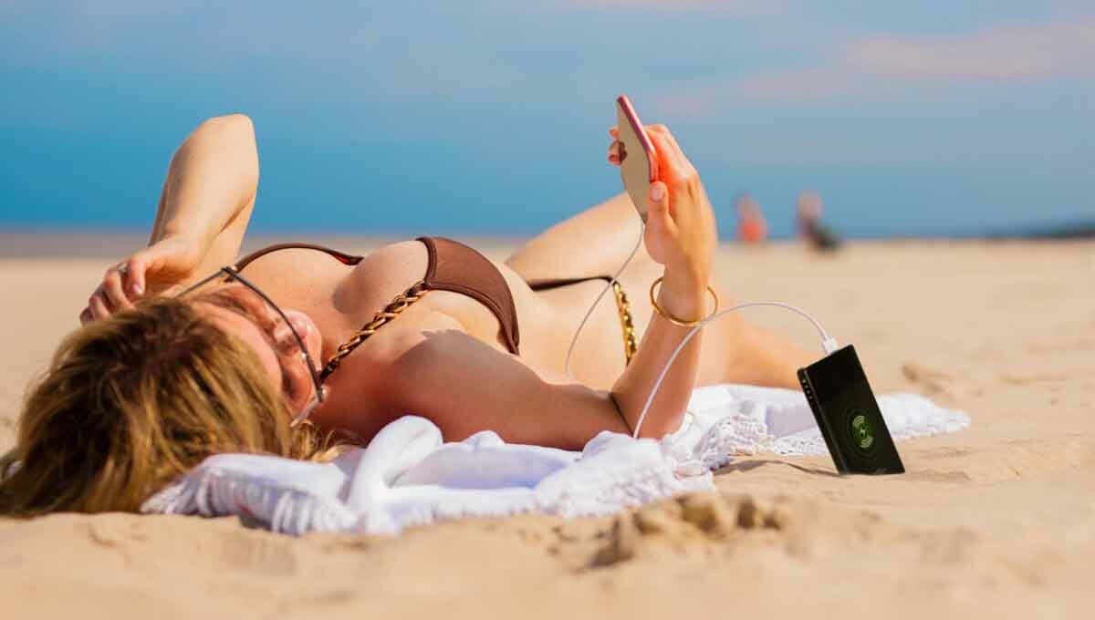sexy woman on the beach with power bank